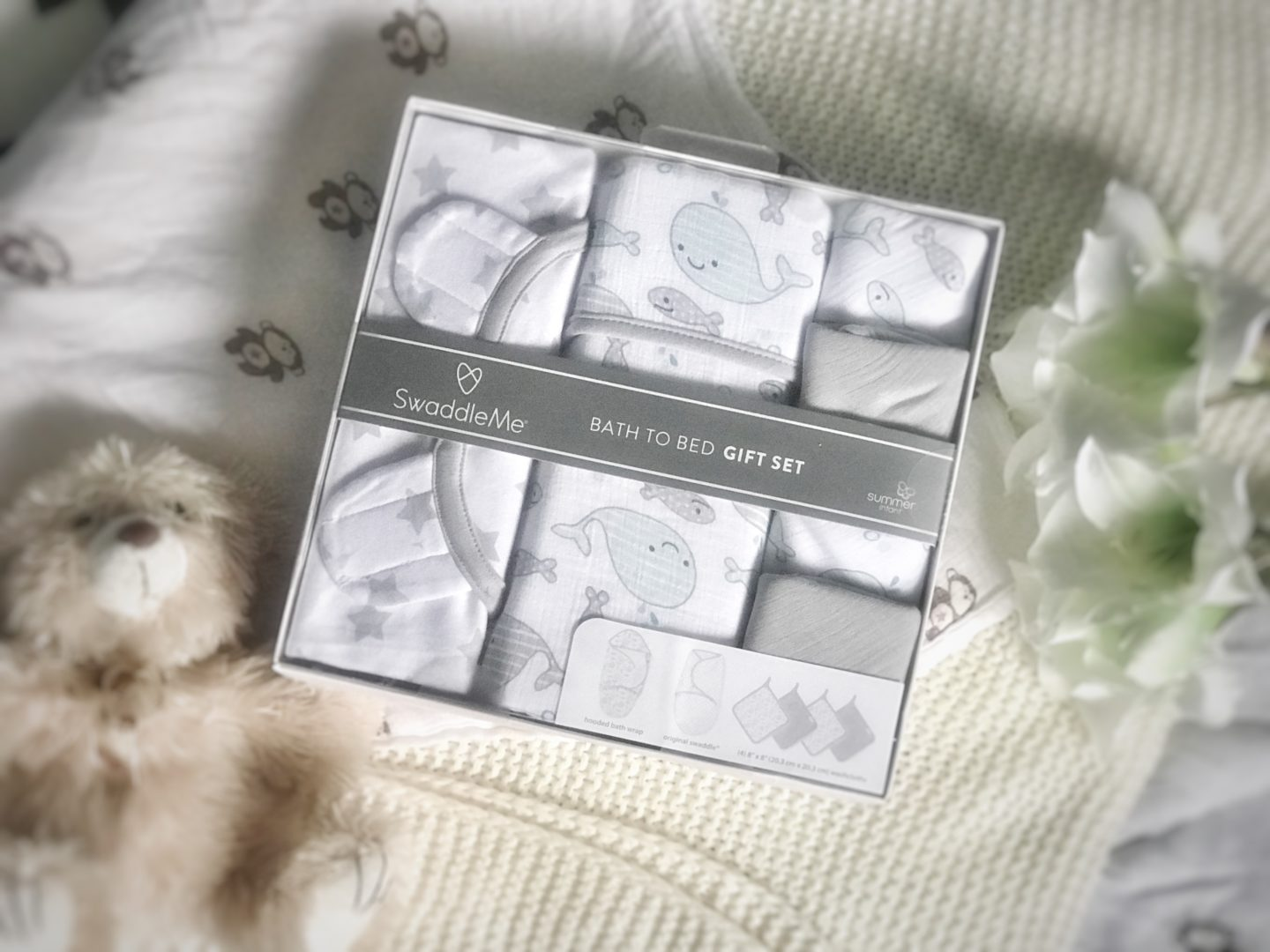 the swaddleme bath to bed gift set in its original packaging next to some fake flowers and a teddy bear
