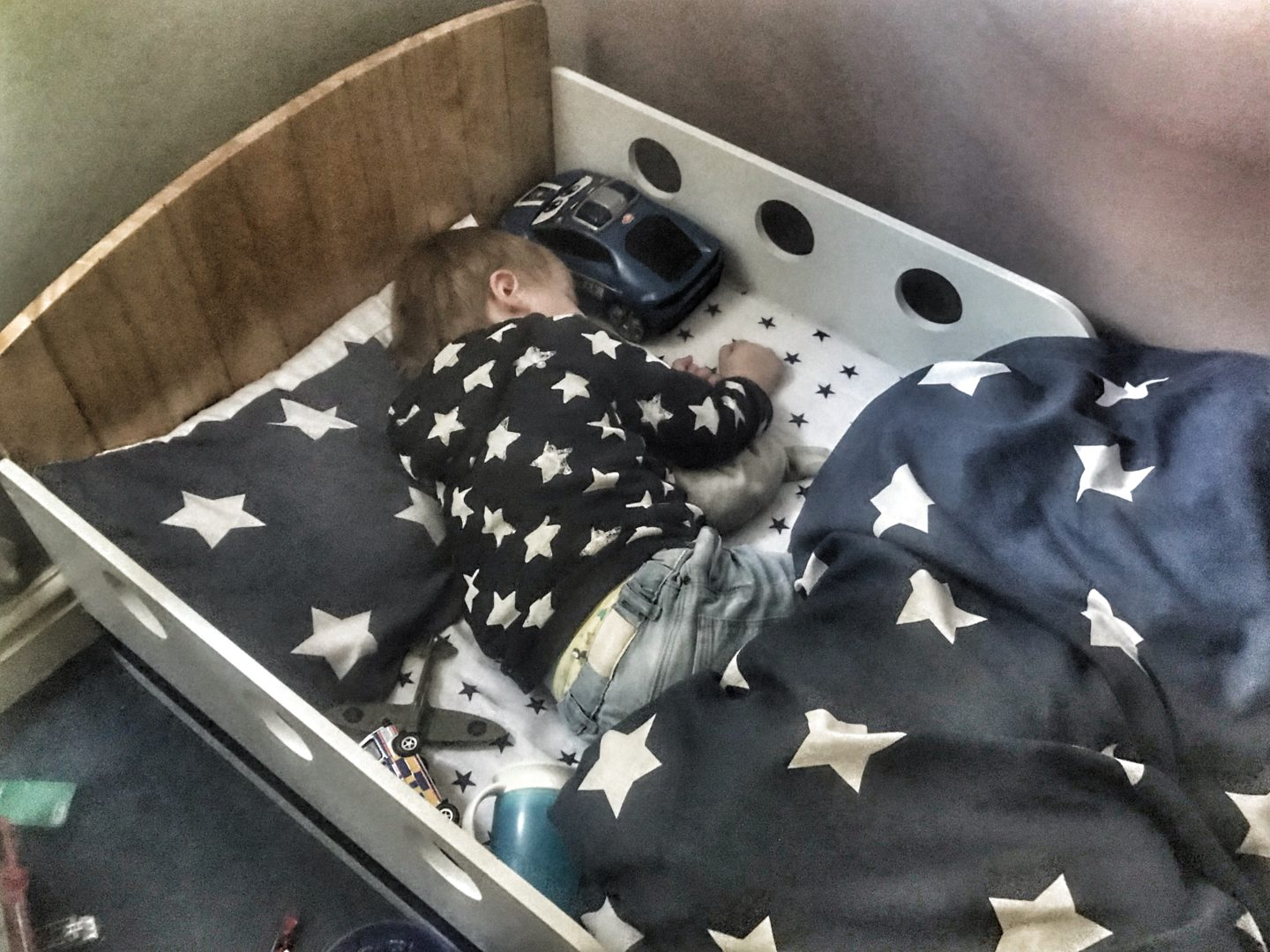 transitioning to a toddler bed, here is Dexter in his toddler bed asleep wearing a navy blue hoodie with white stars and the same style bedding