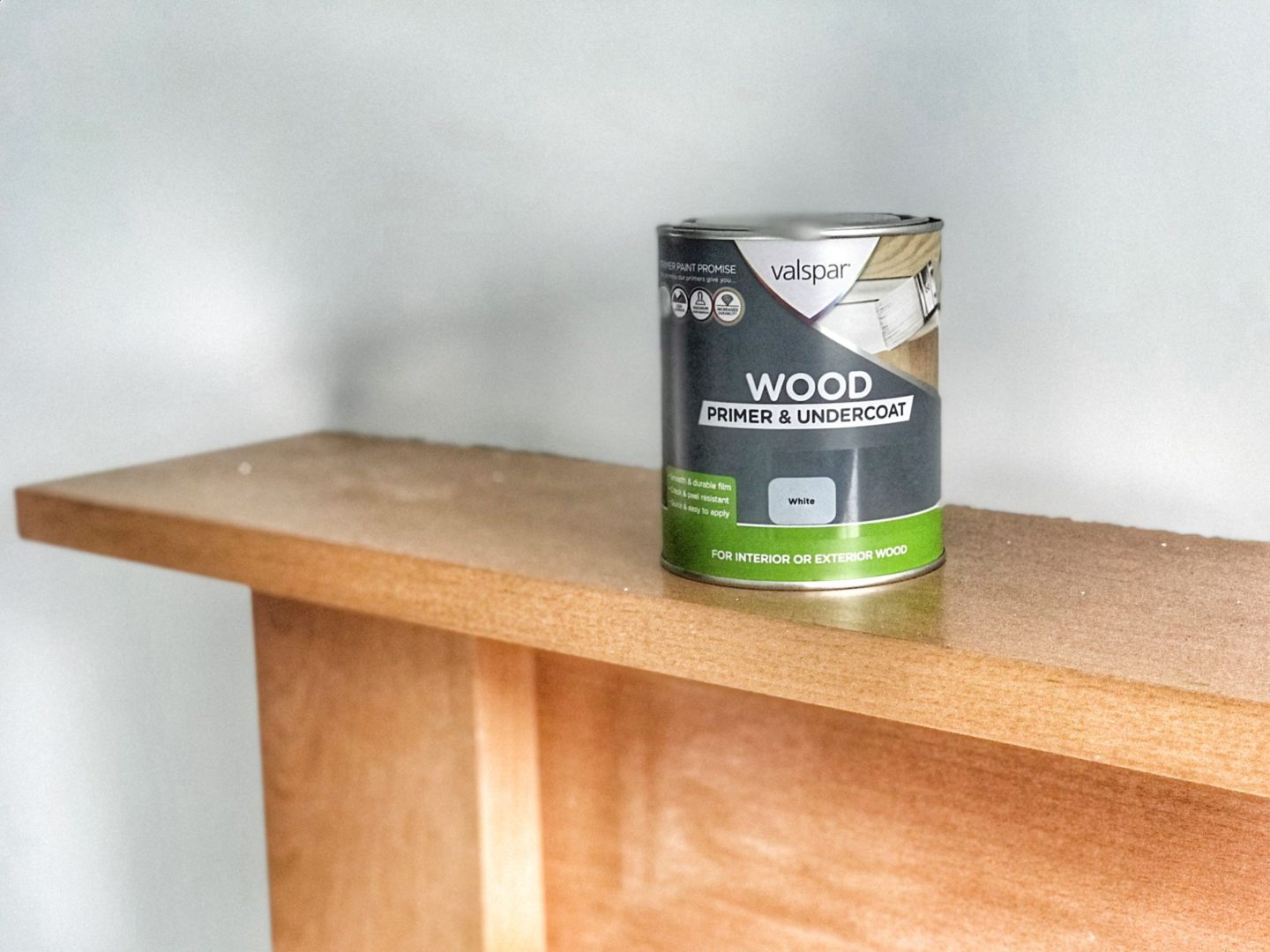 a tin of valspar wood primer rests on top of the wooden fireplace