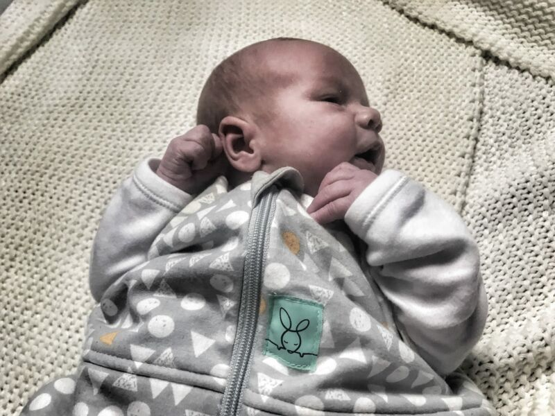 felix wearing the ergopouch cocoon swaddle while lying on a white knitted blanket