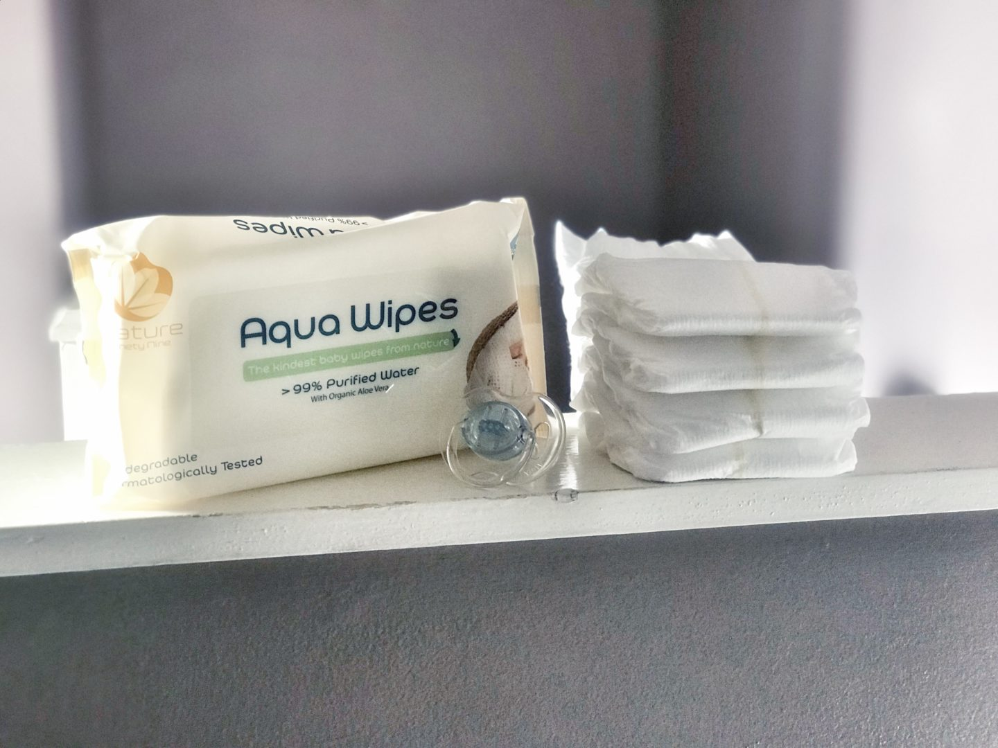 Aquawipes packet and some nappies stacked on a shelf