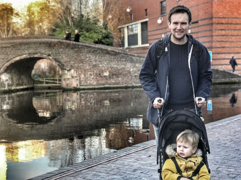 Daddy pushing toddler in the stroller next to the canal on Brindleyplace, Birmingham