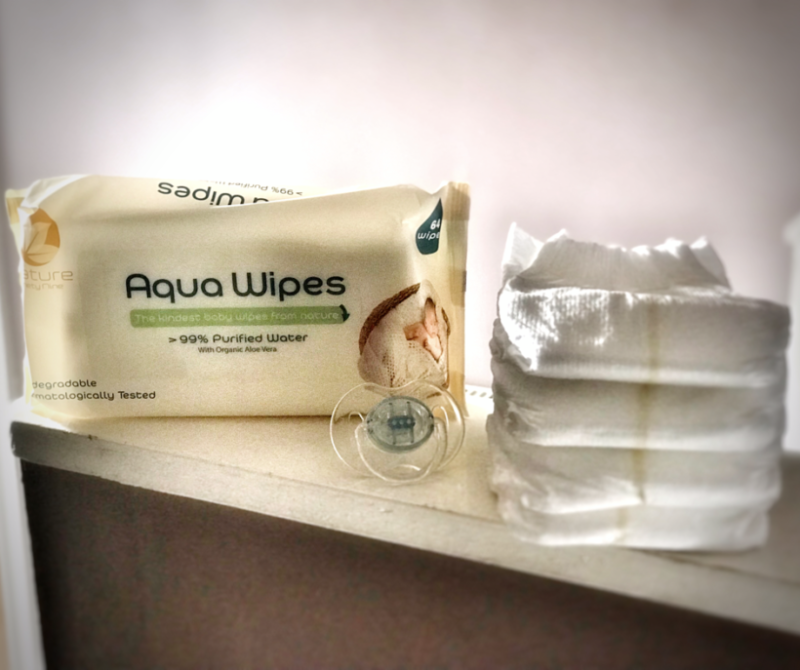 packet of aquawipes and some nappies stcaked on a shelf