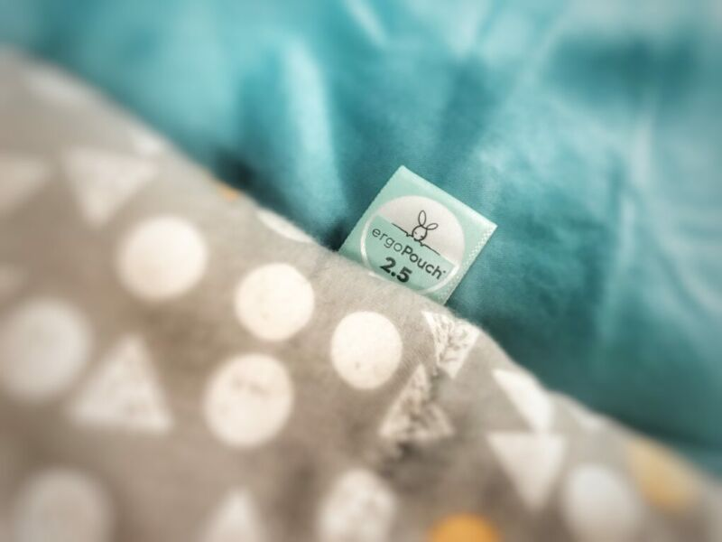 a close up of the ergopouch cocoon swaddle showing it's tag displaying that it's a 2.5 tog