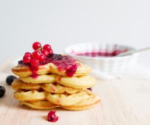 a stack of pancakes with strawberry jam and raspberries on top