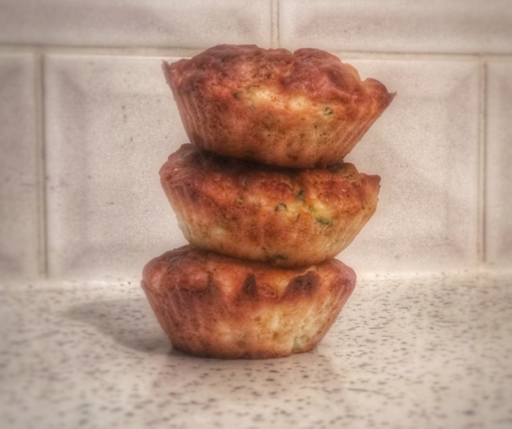 three broccoli and courgette muffins stacked neatly on top of each other