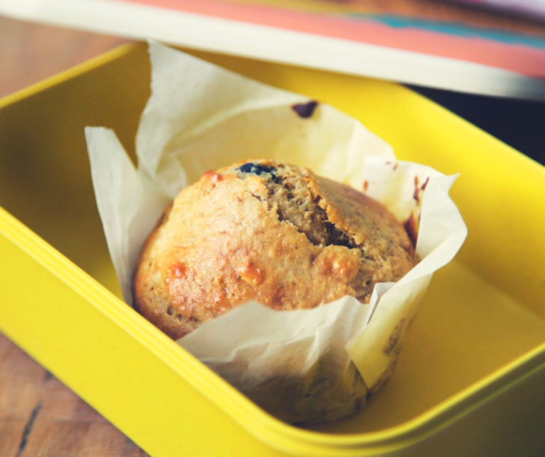 a muffin in a paper case placed in a yellow tupperware bowl