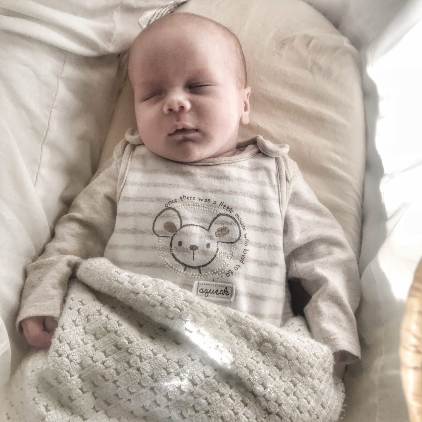 Felix wearing beige dungarees and vest sleeping in his moses basket with a blanket over him