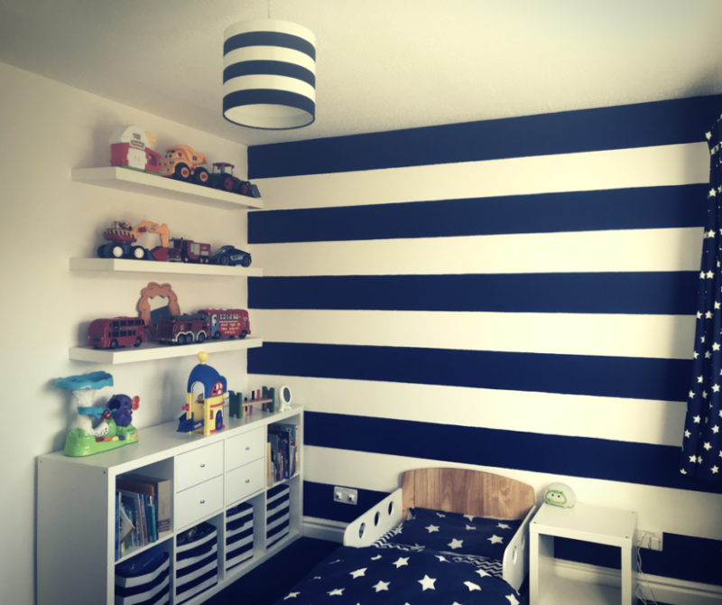 Nautical themed toddler bedroom showing a navy and white striped wall, navy and white lampshade, kallax storage and three wall shelves