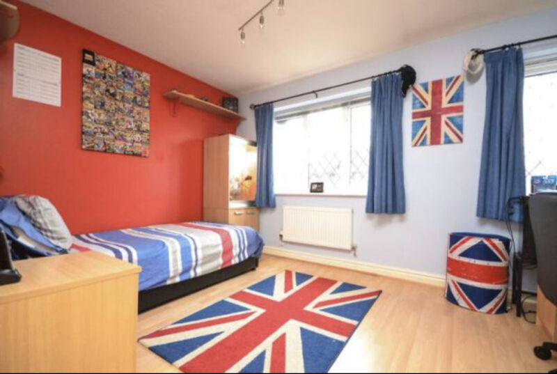 A shot of the toddler bedroom before the makover, a boy's bedroom with a union jack theme, red and blue walls and a union jack rug