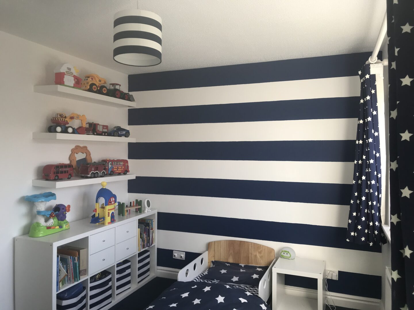 Nautical themed toddler bedroom showing striped navy and white walls, toddler bed, kallax unit and shelves