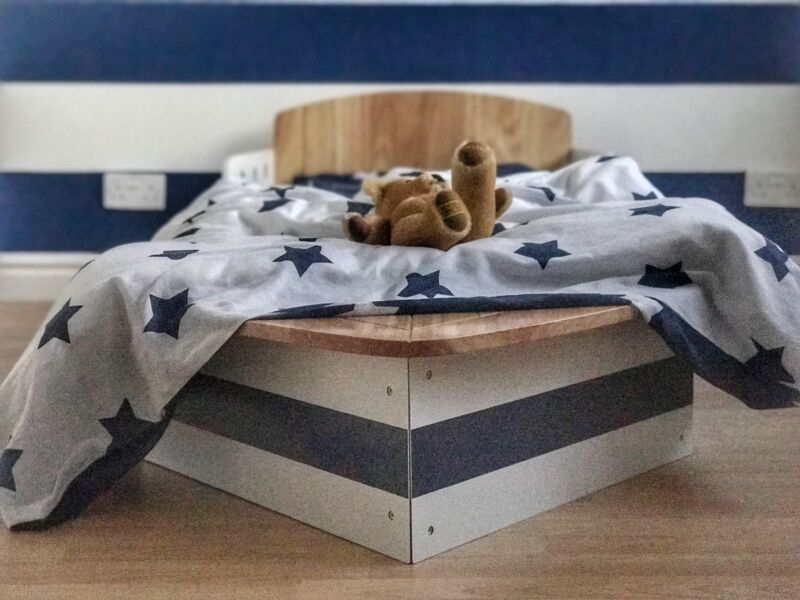 Dexter's toddler bed which is shaped like a boat with a white duvet with navy blue stars and a teddy bear placed on top