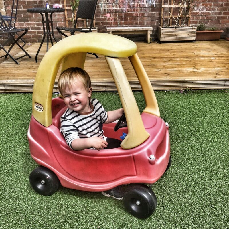 Dexter driving the little tikes cozy coupe on artifical grass outside