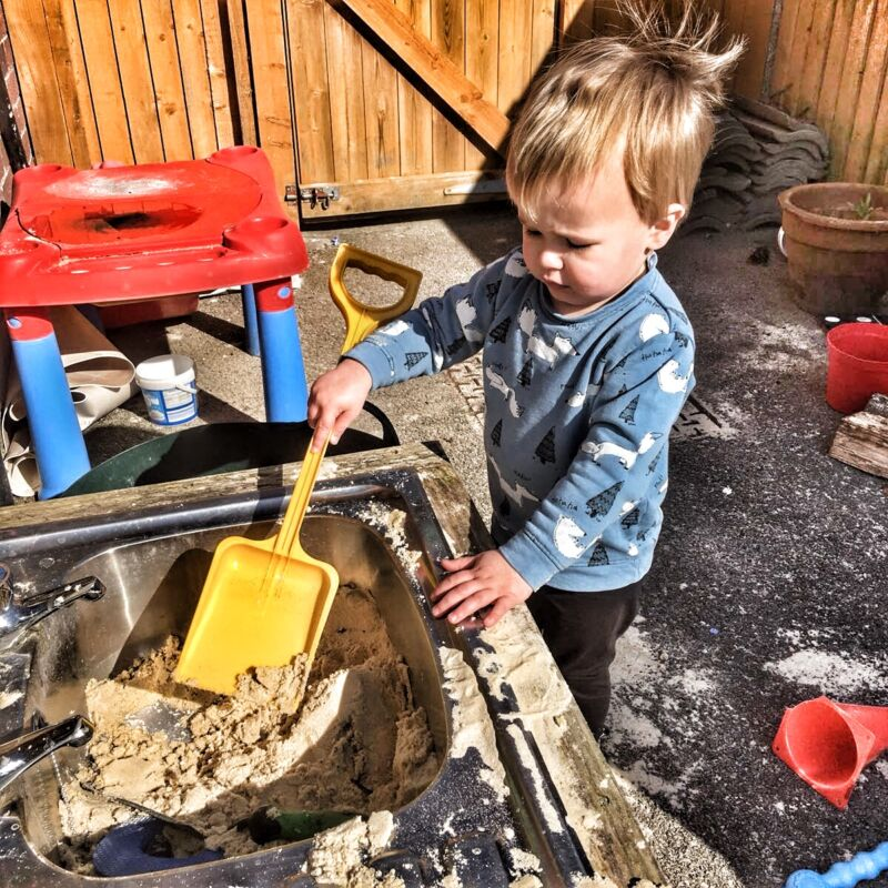 Dexter playing outdoors in a sandpit holding a yellow spade