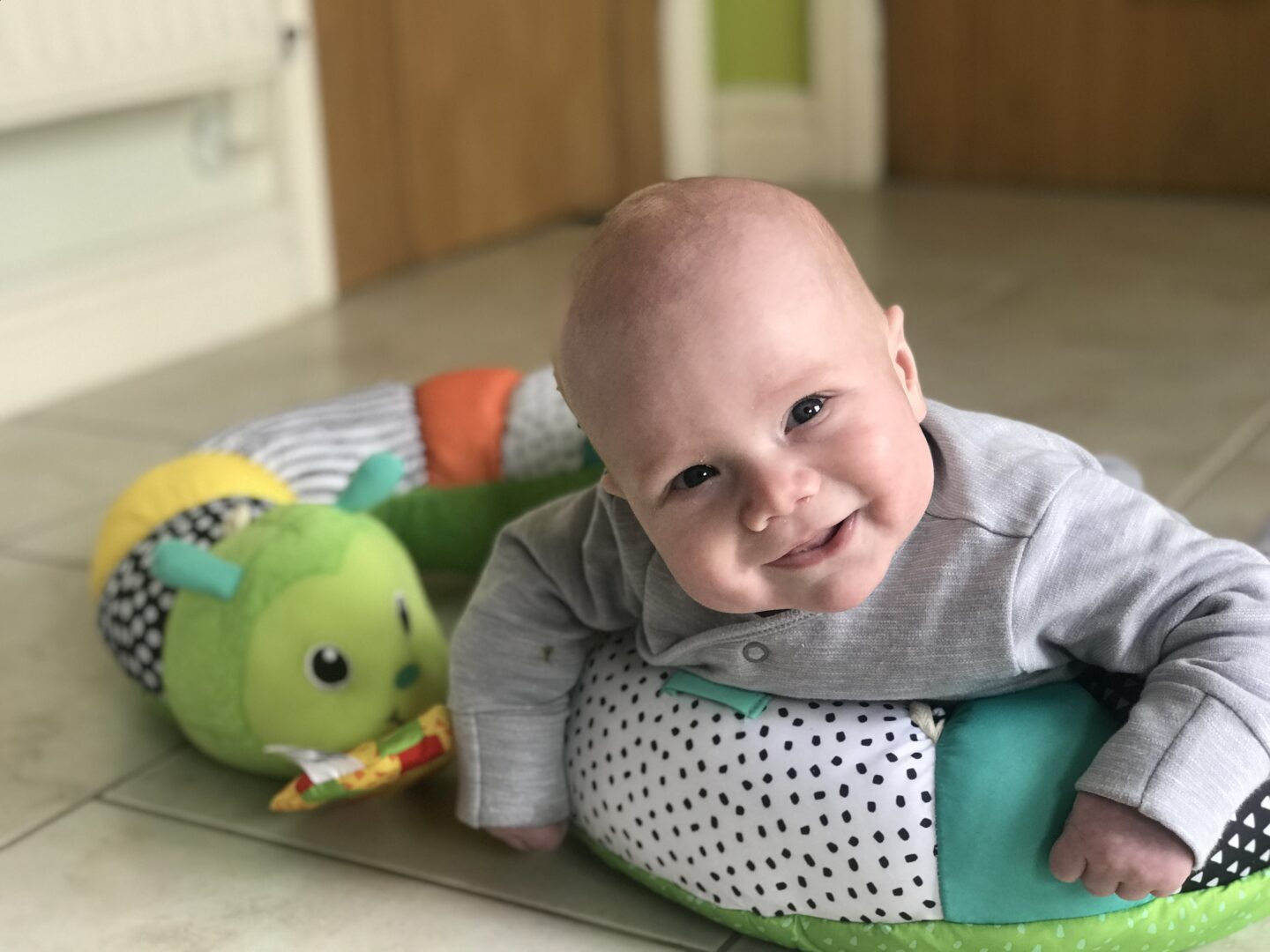 Felix using the Infantino Prop-a-Pillar tummy time support in the kitchen smiling happily