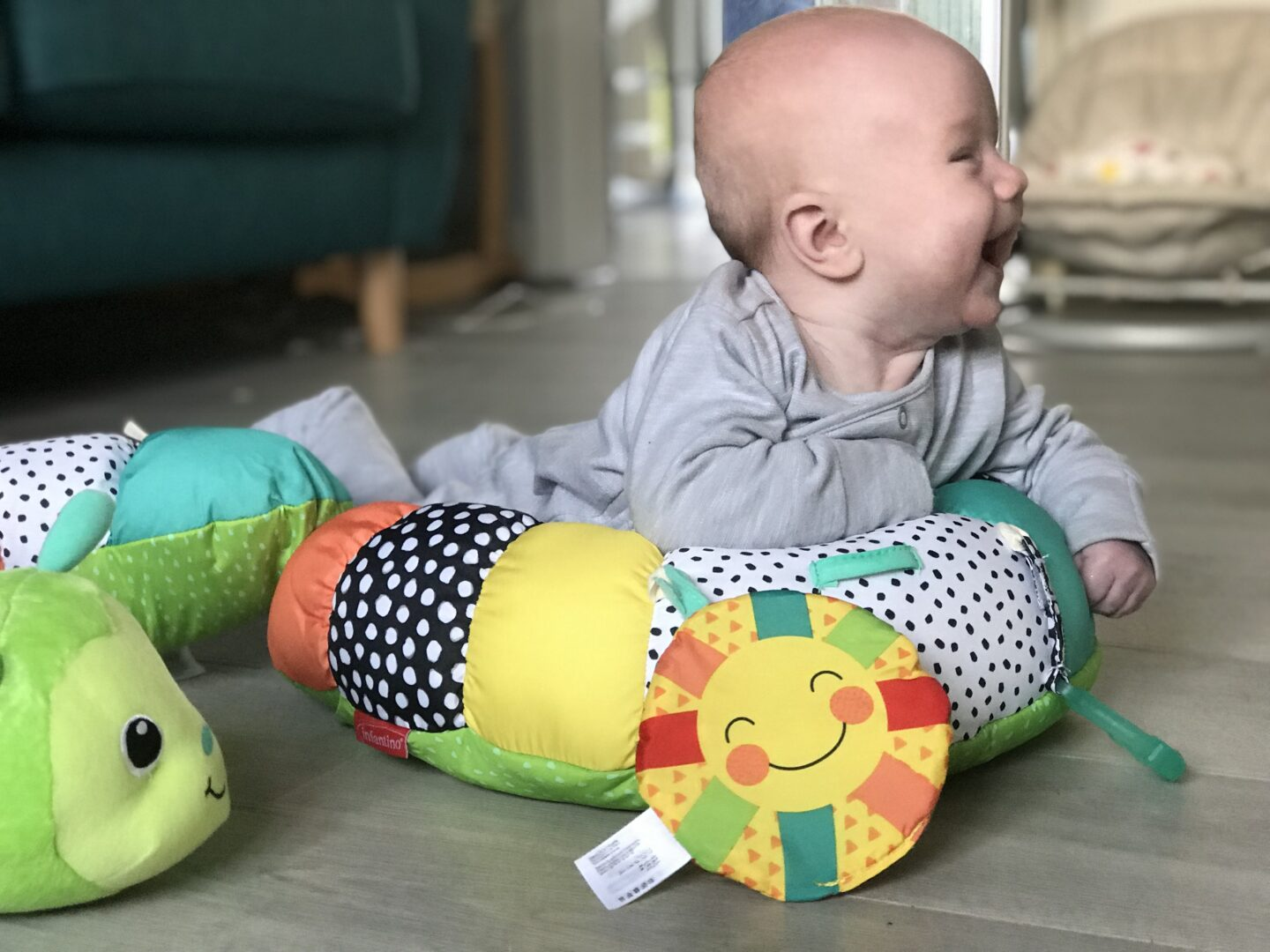 Felix using his Infantino Prop-a-Pillar tummy time support in the lounge, propping himself up and laughing