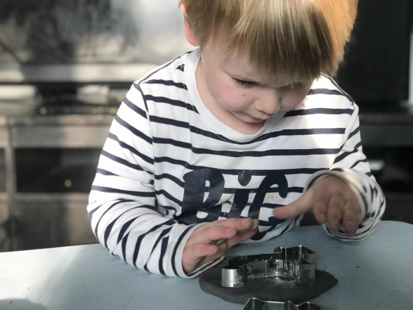 Dexter putting a cookie cutter into some black playdough that we handmade