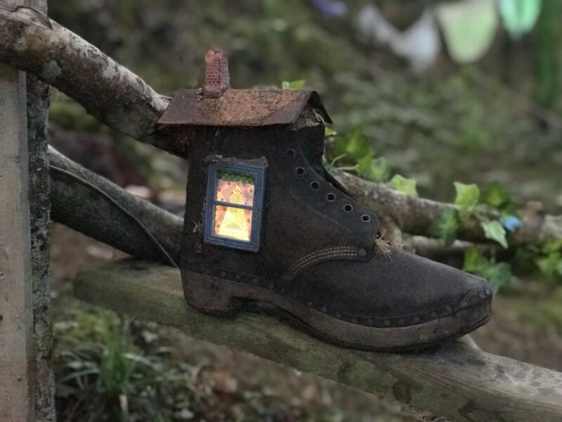 a house made out of a boot sat on a tree stump in Bluestone's enchanted forest