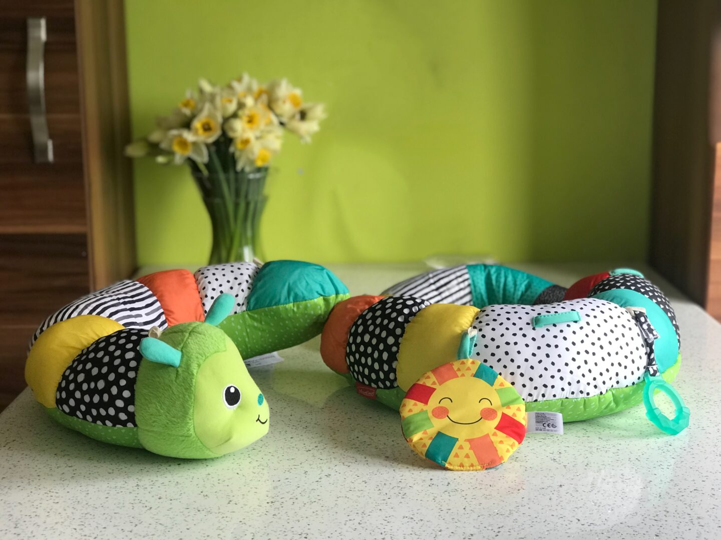 The Infantino Prop-a-Pillar tummy time support placed on kitchen table with daffodils in a vase in the background