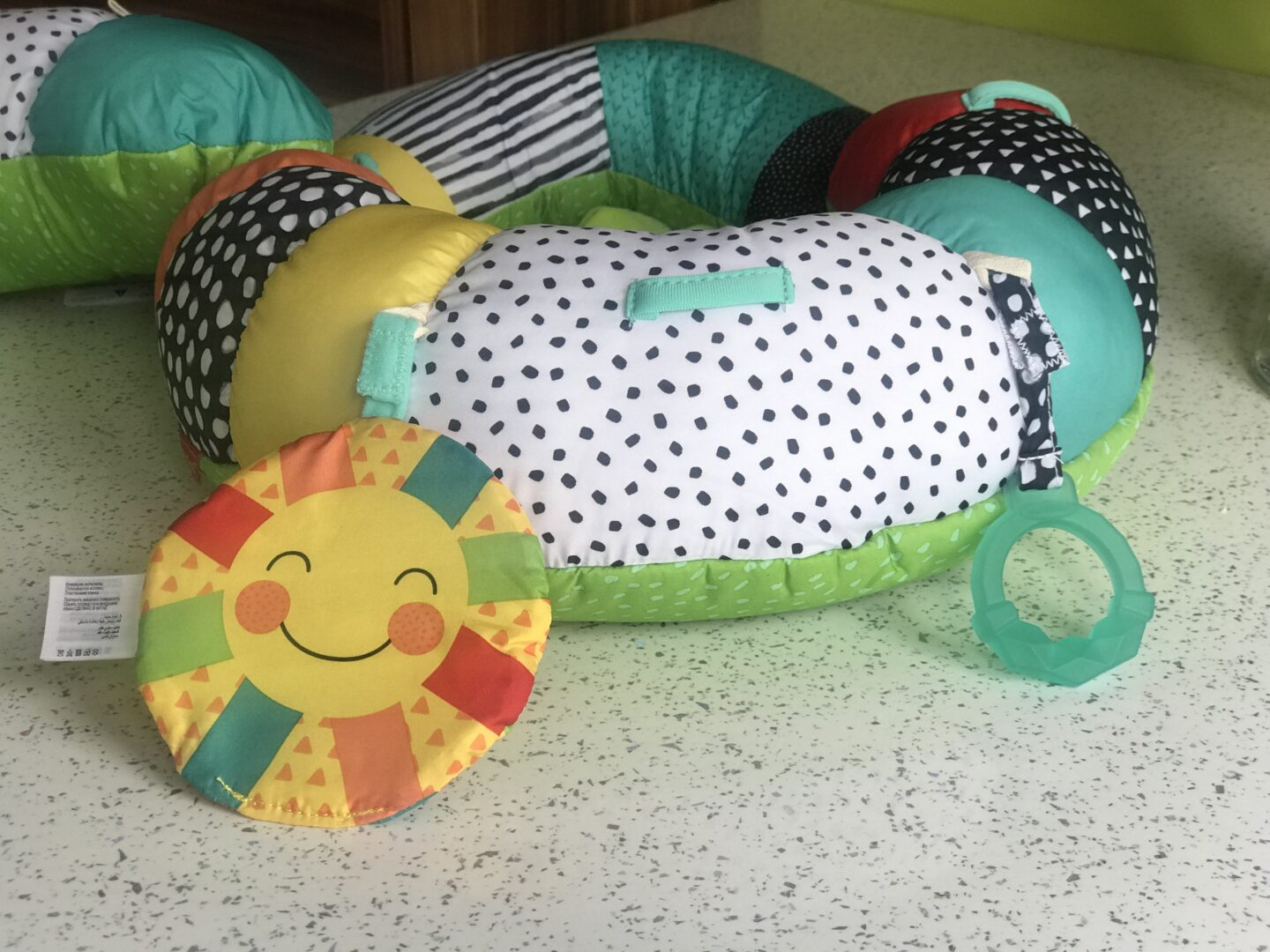 A close up of the Infantino Prop-a-Pillar tummy time support showing the crikly sun and BPA-free teether