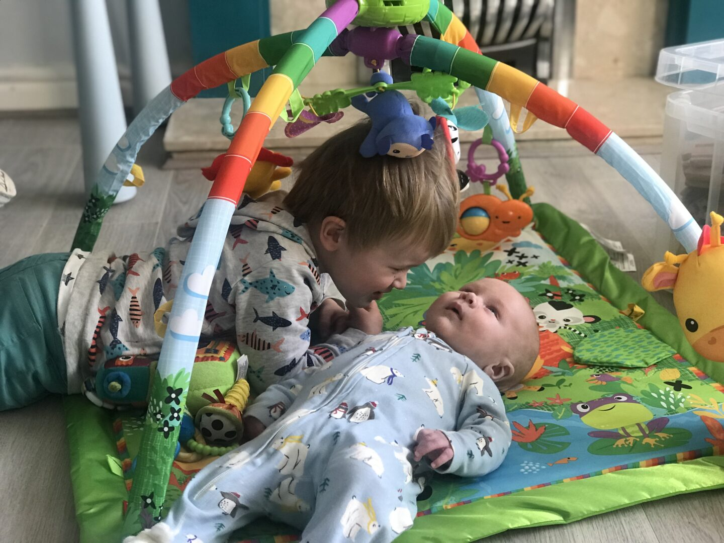 Felix lying on the playmat looking at a toy with his brother Dexter looking at him
