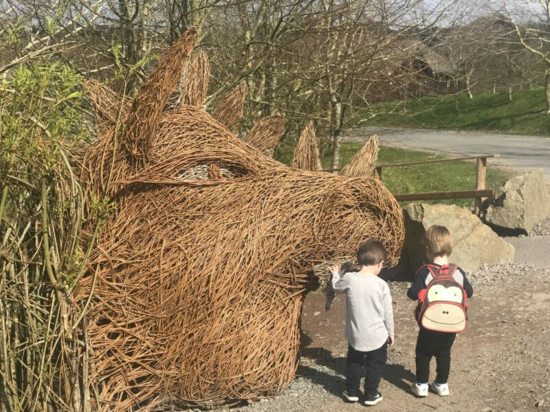 reuben and dexter next to a huge bull's head made out of twigs in Bluestone Wales