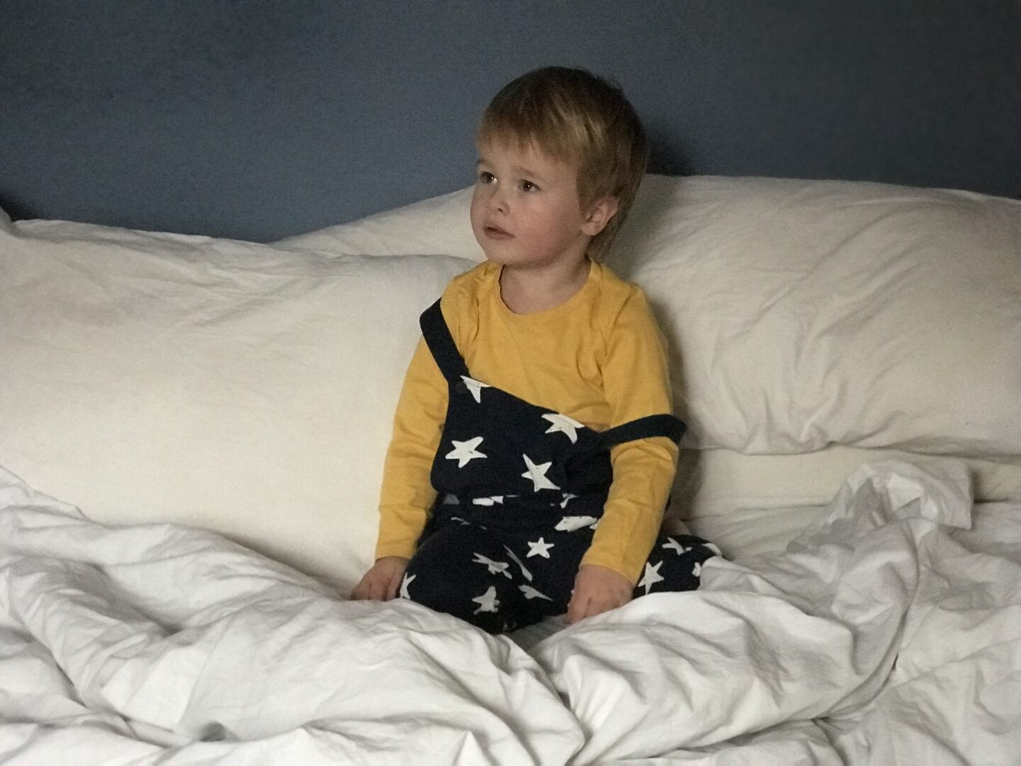 Dexter sitting on the bed wearing a yellow t shirt and navy blue dungarees with white stars on