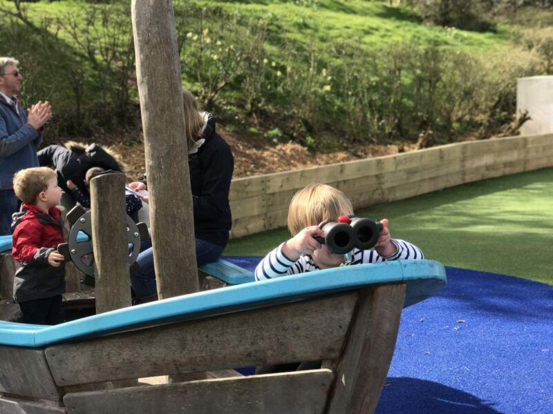 dexter in a pirate ship using toy binoculars in bluestone's playground