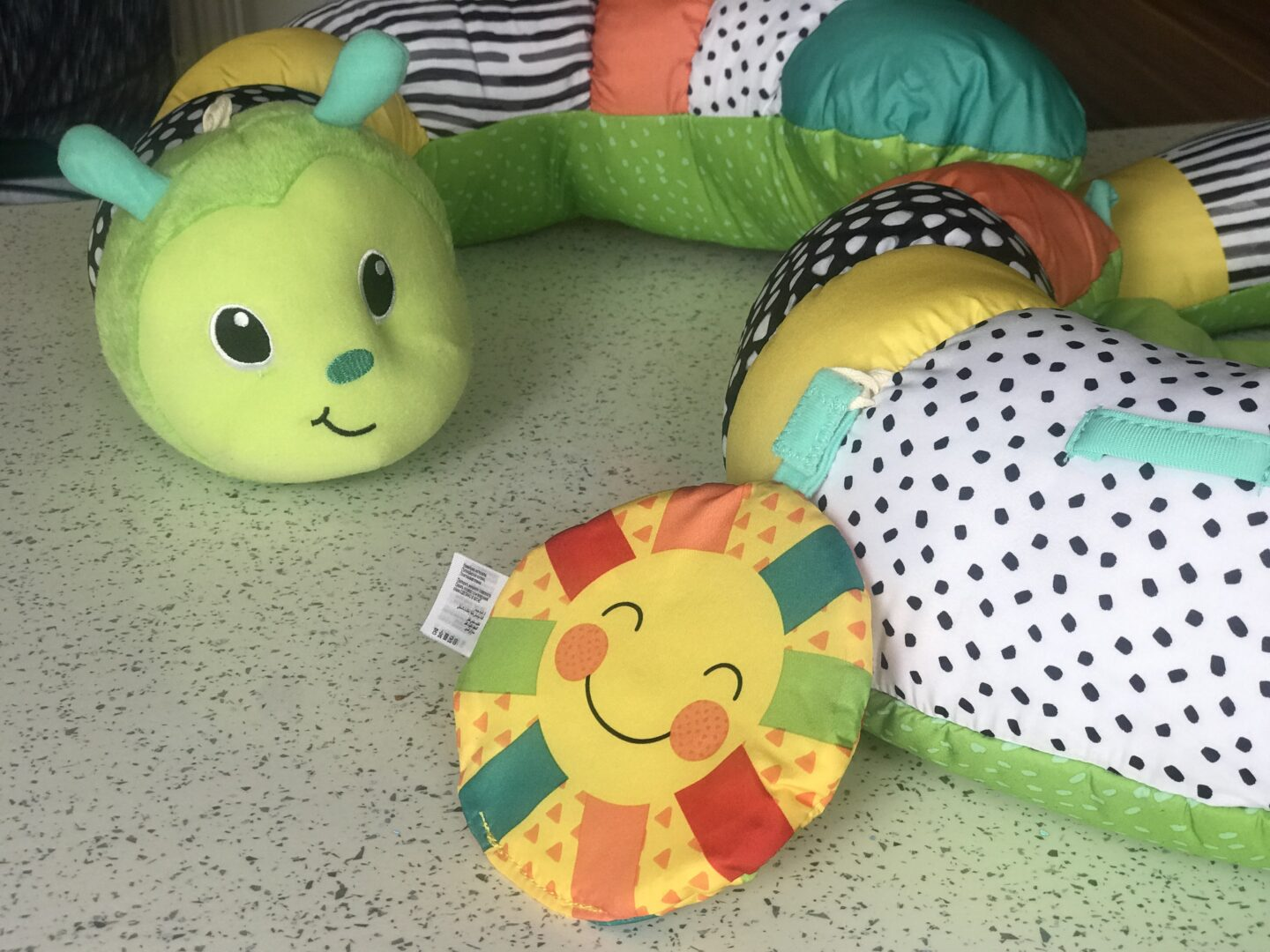 A close up of the Infantino Prop-a-Pillar tummy time support showing the crinkled sun and caterpillar's face