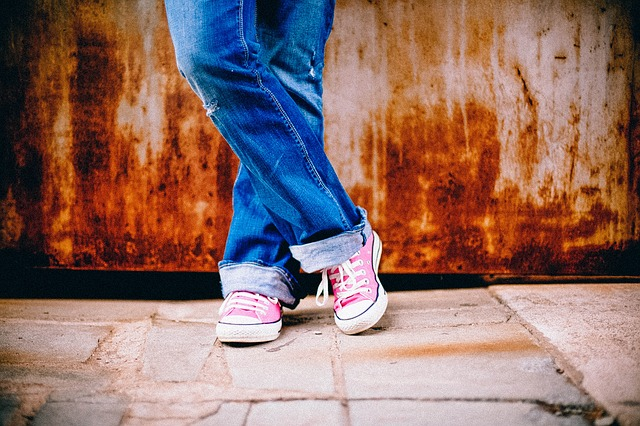 woman's legs wearing jeans and pink shoes stood on a tiled floor