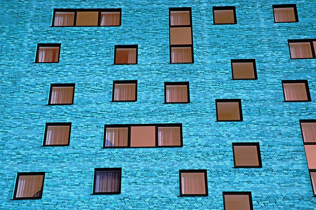 block of flats showing blue brickwork and lots of windows