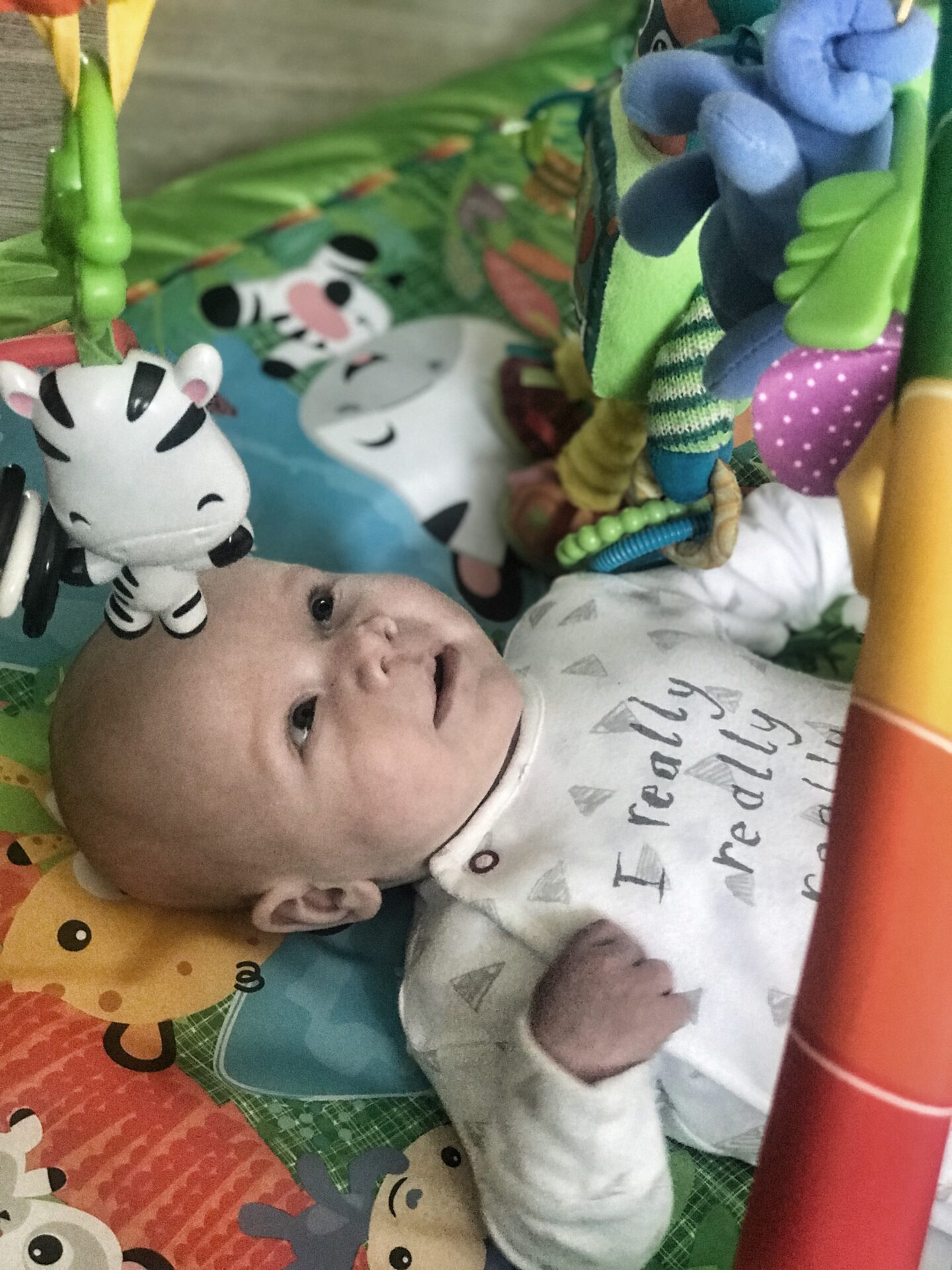 Felix lying on his Fisher Price playmat looking up at a toy