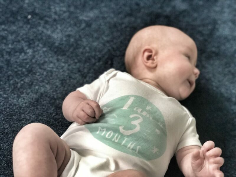Felix lying on a blue carpet wearing a white short sleeved vest which says I am three months old, looking away from the camera to his left