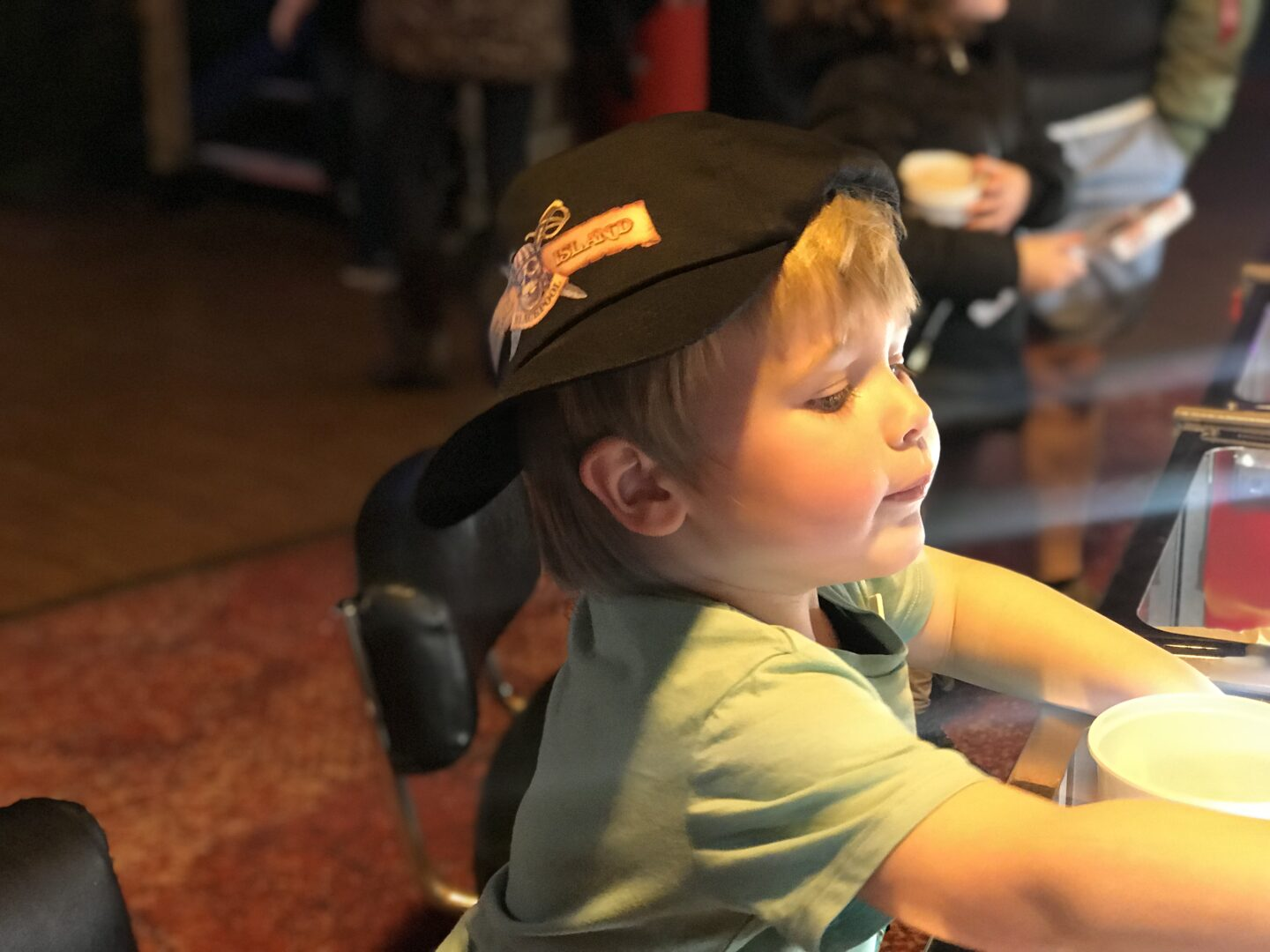 Dexter wearing a coral island hat, playing on the 2p machines