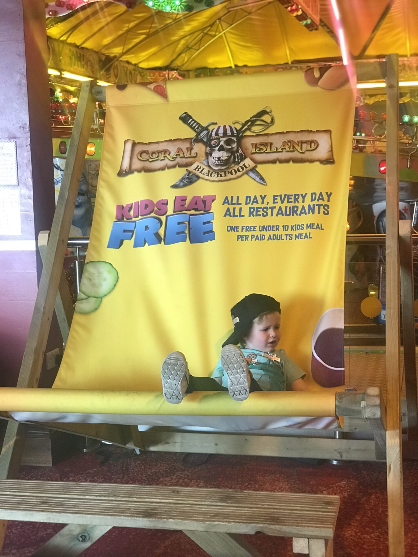 Dexter sat on a giant yellow deckchair which says kids eat free, in coral island, blackpool
