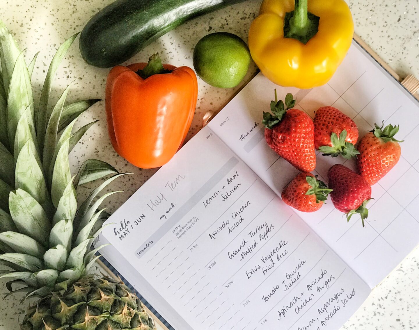 A diary with a meal plan on each day's surrounded by brightly coloured fruit and vegetables