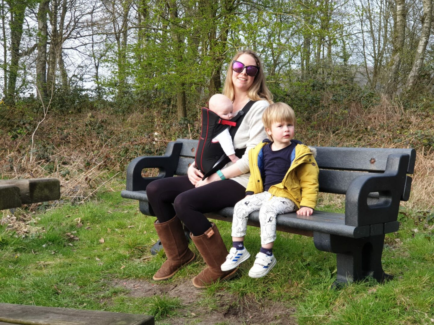 Nicola babywearing Felix and Dexter sat on a bench in Mere Sands Woods