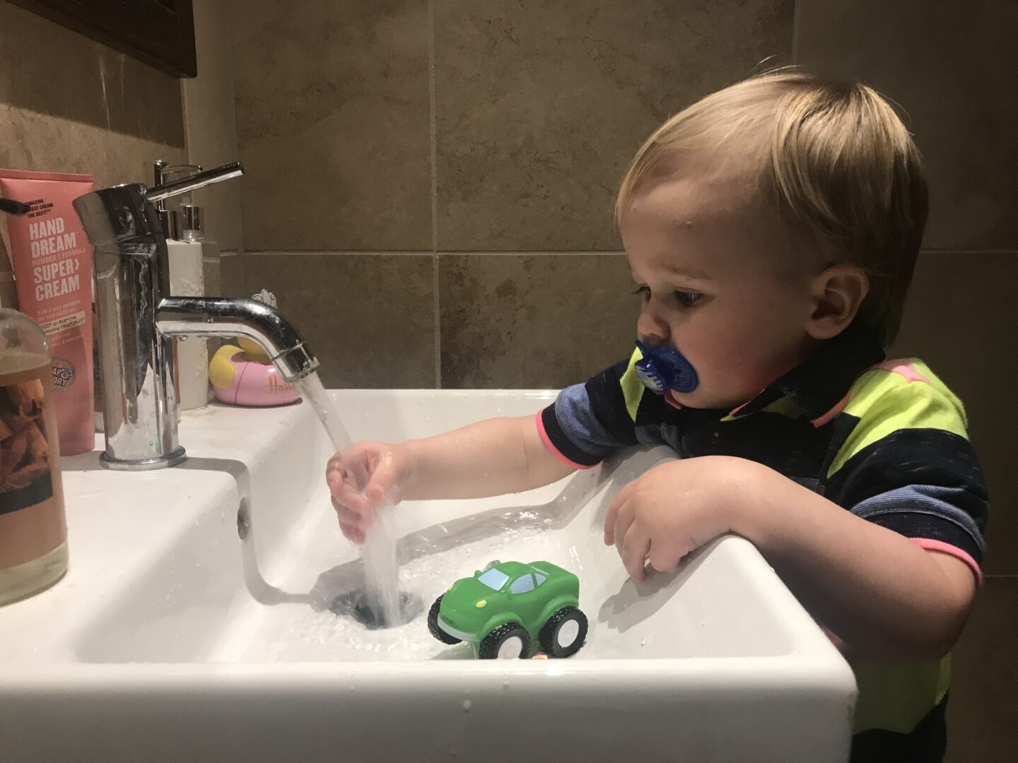 Dexter playing with the tap over a sink in the bathroom using a blue dummy