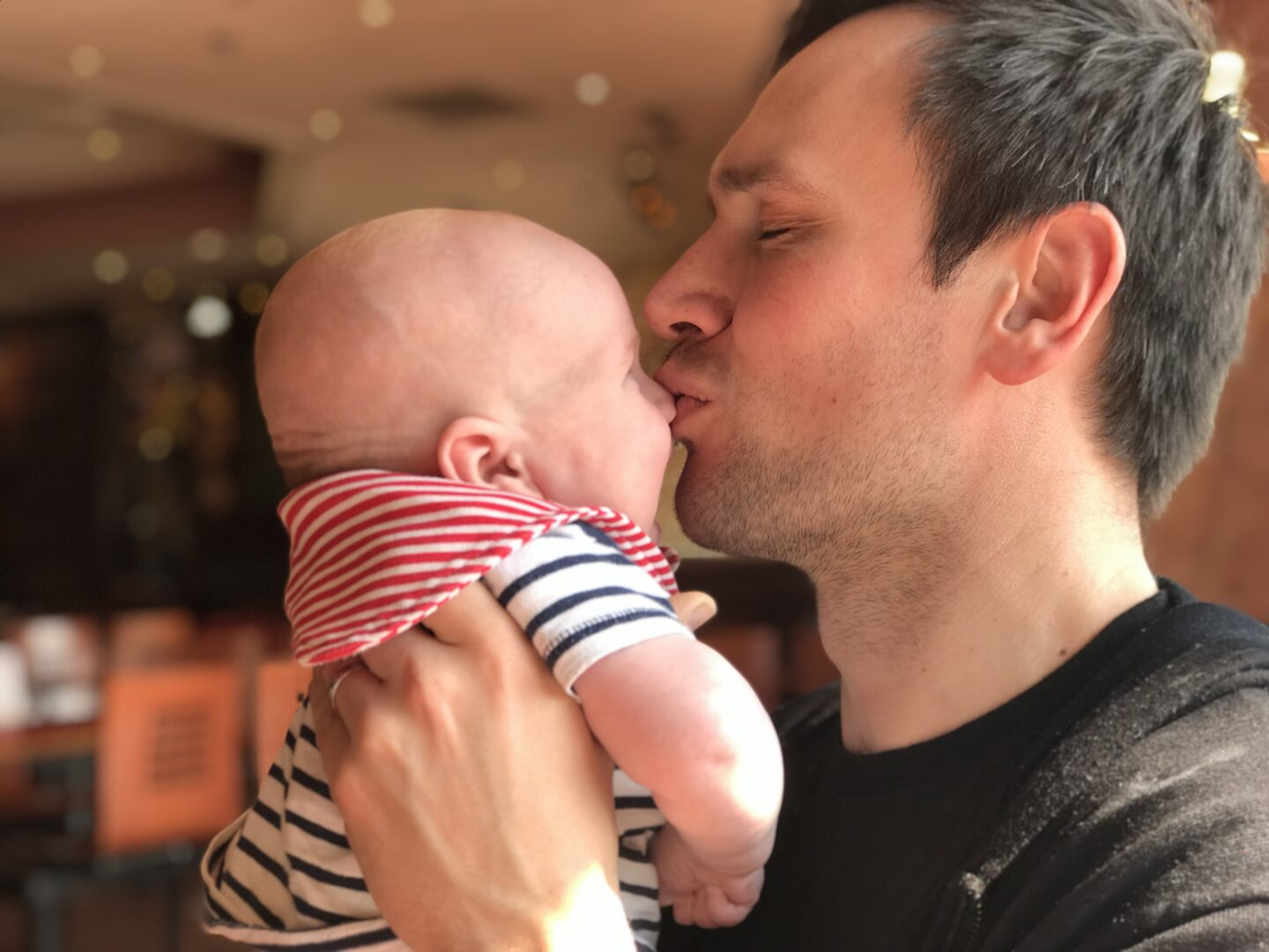 Neil holding Felix and giving him a kiss on the nose