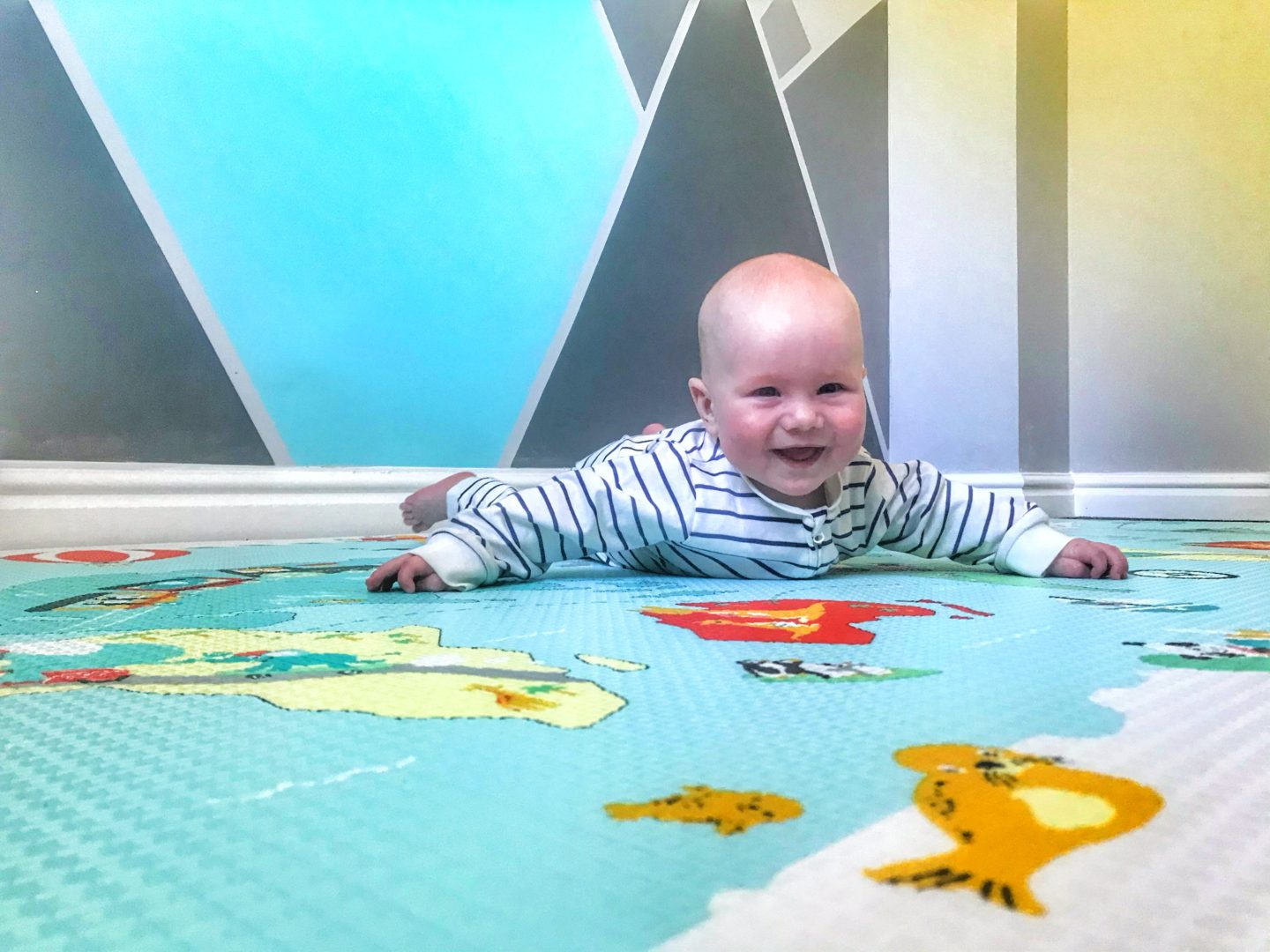 Felix doing tummy time on the Skip Hop Reversible playmat With a big smile on his face