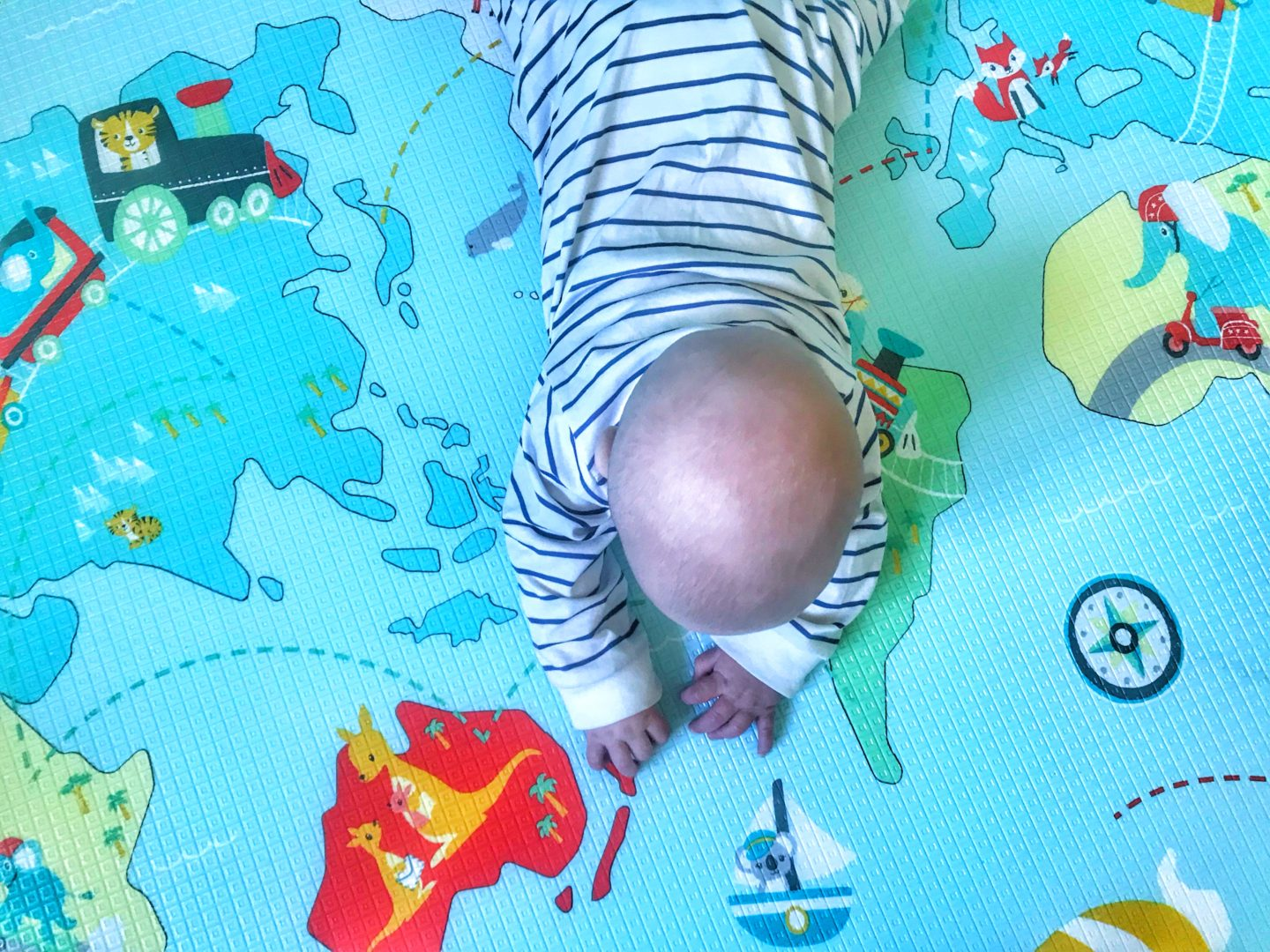 View from above of Felix doing tummy time on the Skip Hop Reversible playmat