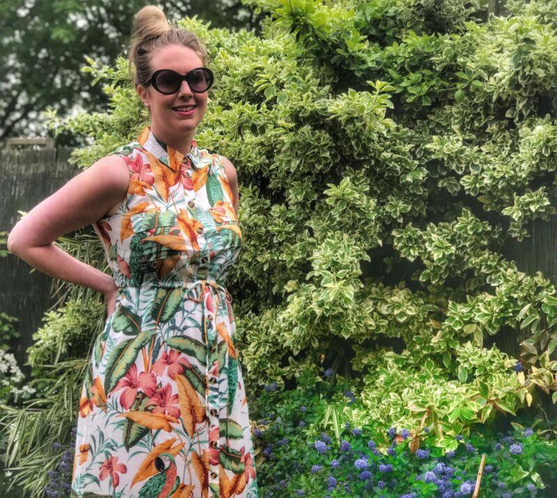 Nicola stood in garden wearing Warehouse parrot midi dress