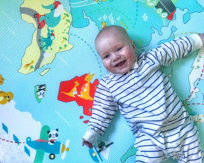 Felix on his back on the Skip Hop Reversible playmat