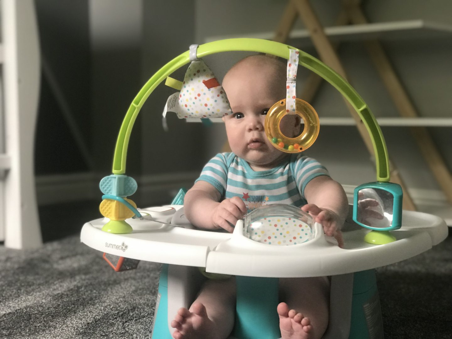 Felix in his Summer Delux 4 in 1 Superseat looking at dangling toys
