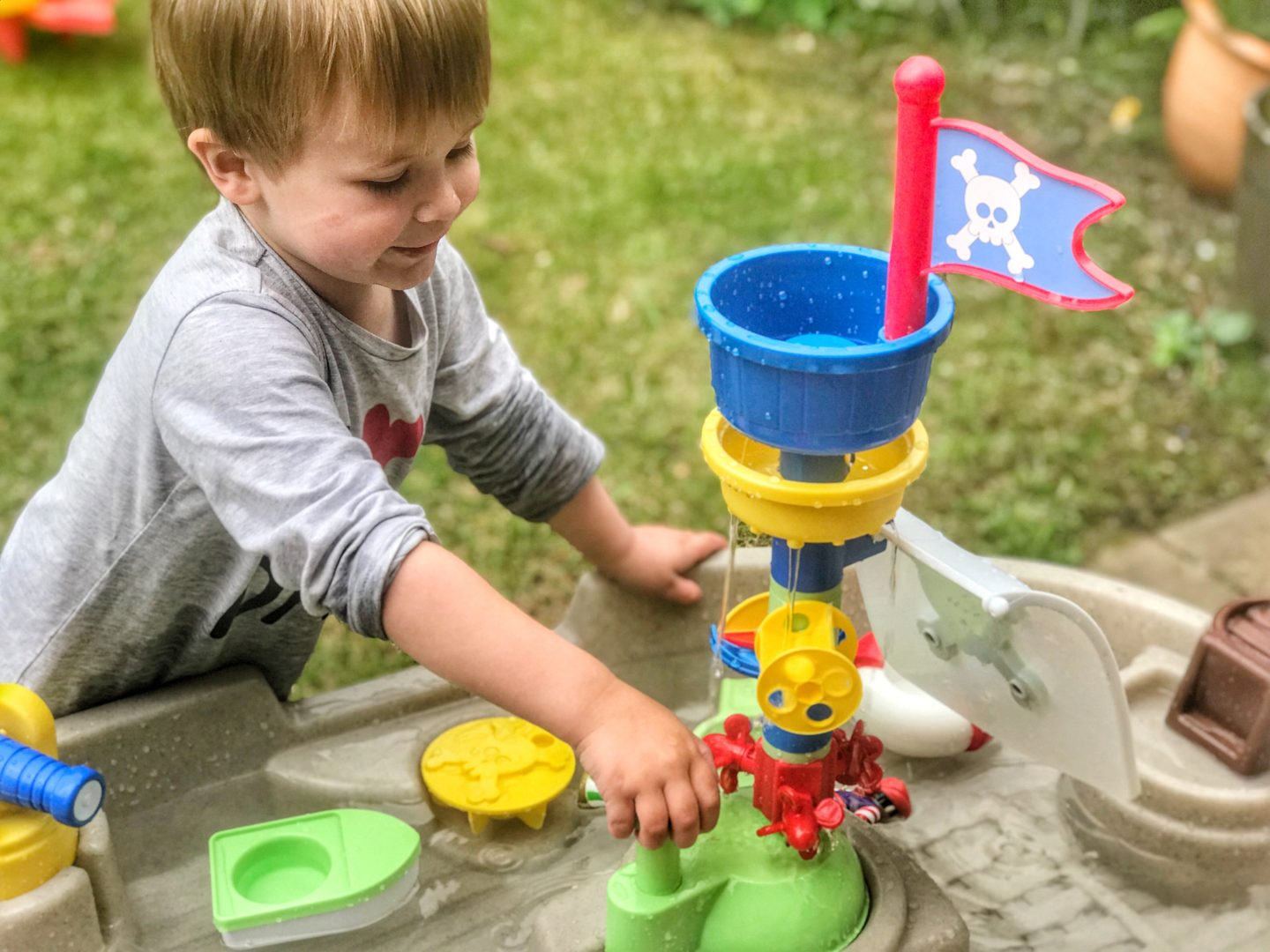 Dexter pushing the pump on the Little Tikes anchors away pirate ship water table