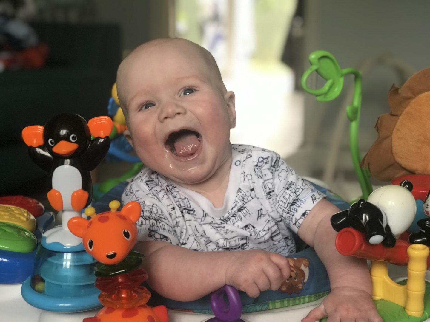 Felix with a huge smile on his face while in husband baby Einstein activity centre