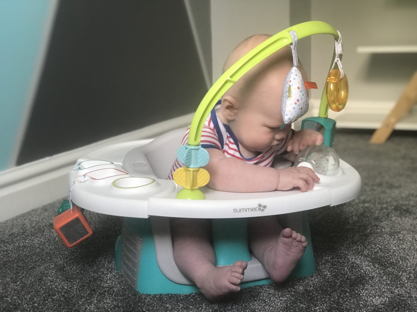 Felix in his Summer Delux 4 in 1 Superseat looking at the activity wheel