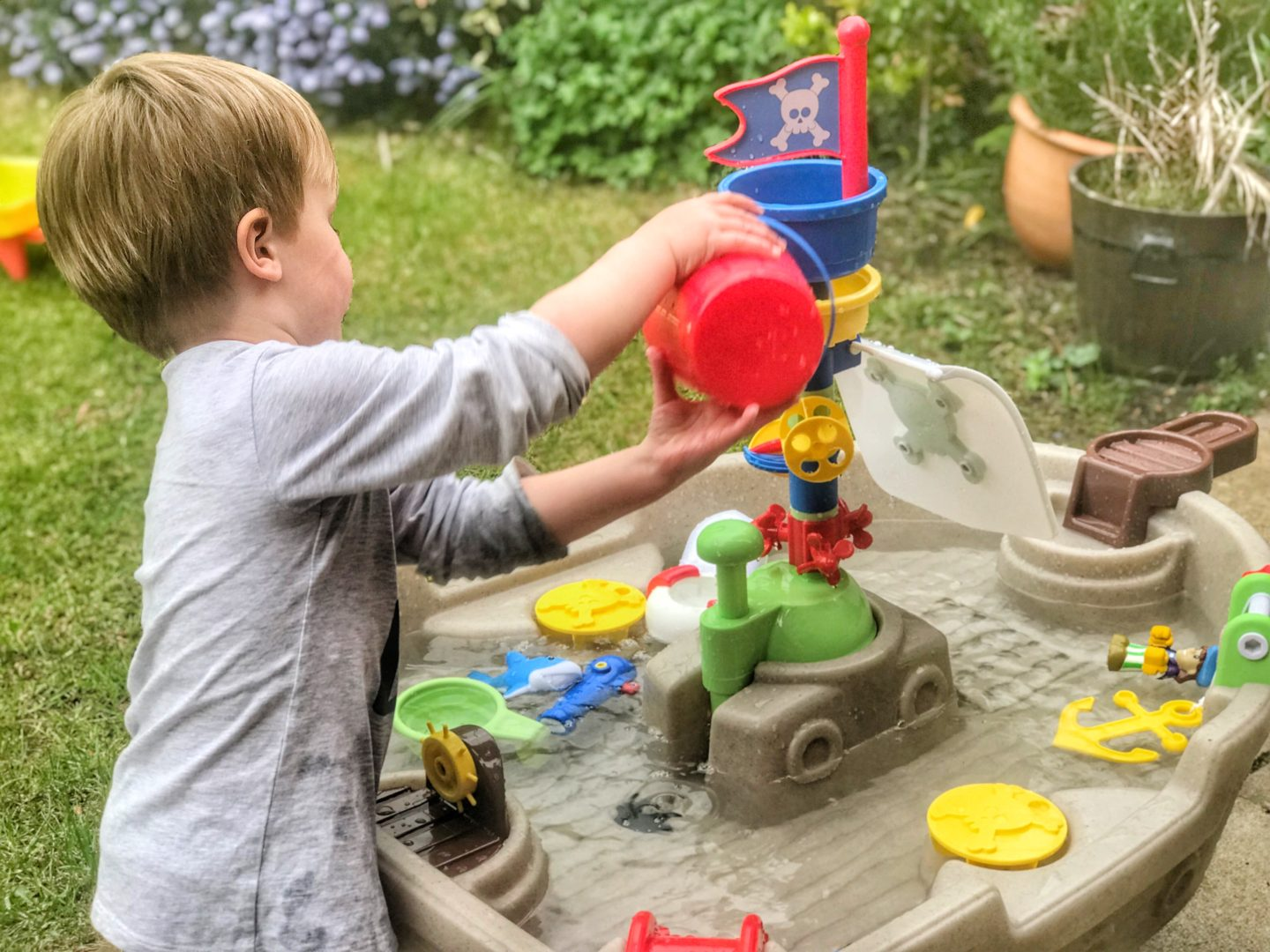 Dexter playing with the red bucket of the Little Tikes anchors Away pirate ship water table