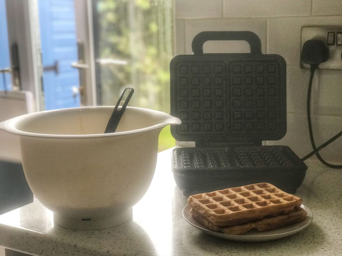 Waffles for babies next to waffle maker and white bowl in kitchen