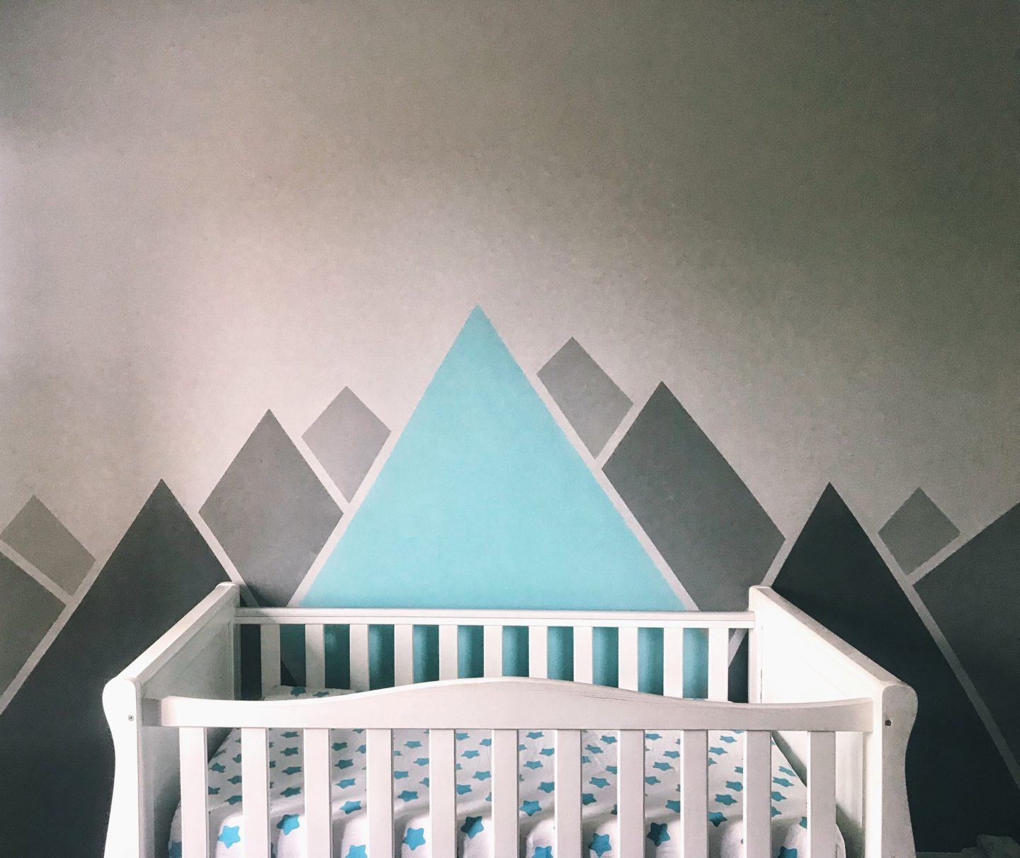 Felix's Bedroom - grey and aqua mountains painted on the wall behind a white cot